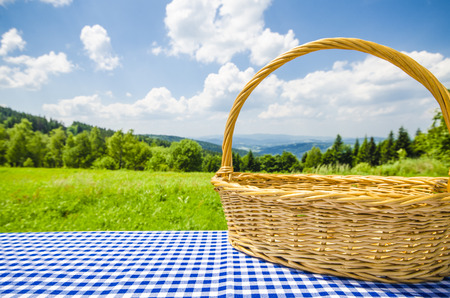 picnic cloth: Empty table with wicker basket and landscape background
