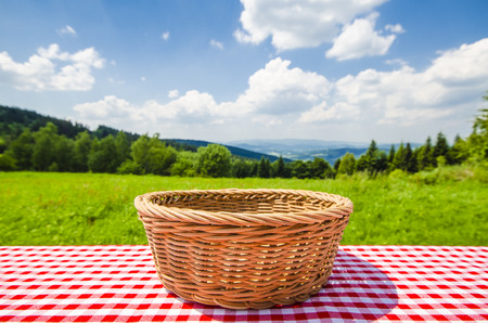 Empty table with wicker basket and landscape background