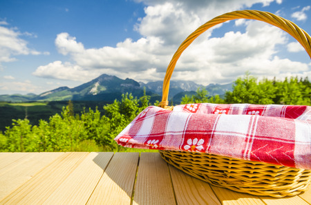 Empty table and wicker basket with landscape background