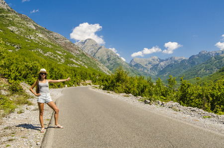 hitchhiking: Young attractive woman hitchhiking along empty road Stock Photo