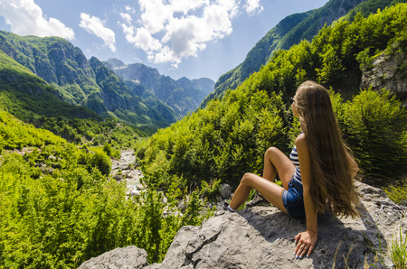 mountain valley: Young woman sitting on a rock and looking at beautiful mountains