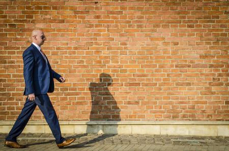 gente exitosa: Hombre de moda joven en un juego contra la pared de ladrillo