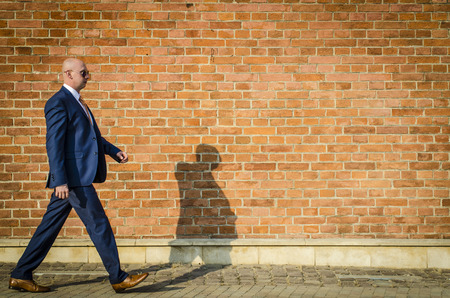 person walking: Young fashionable man in a suit against brick wall