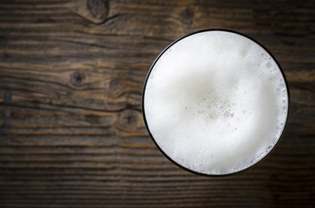 木製のテーブルの上のビールの泡のガラス