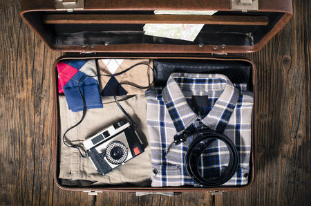 open suitcase: Vintage travel suitcase on wooden table