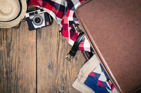 Travel suitcase with clothes, old camera and straw hat on wooden table