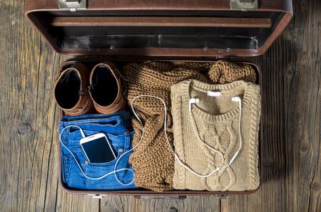 カジュアルの服の女性とレトロなスーツケース