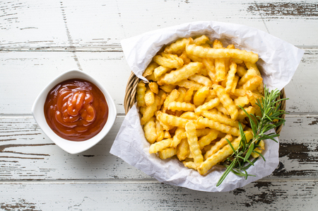 papas fritas: Patatas fritas con la salsa de tomate sobre tabla de madera. Vista superior