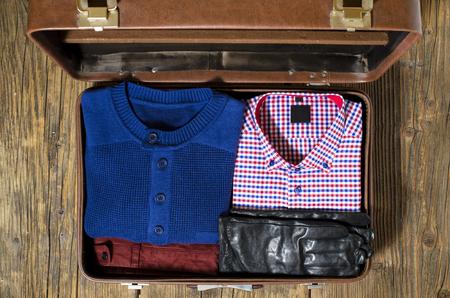 服カジュアルな男とオープン旅行スーツケース。トップ ビュー