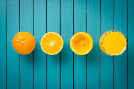 Fresh oranges and orange juice on wooden table