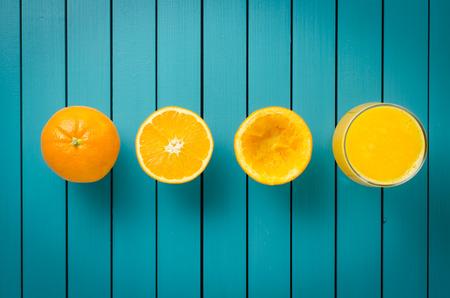 Fresh oranges and orange juice on wooden table