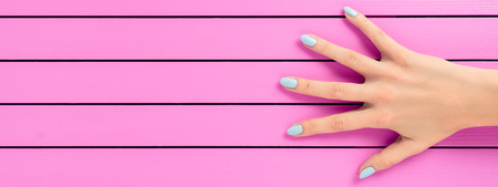 Female hand with blue nails over pink background