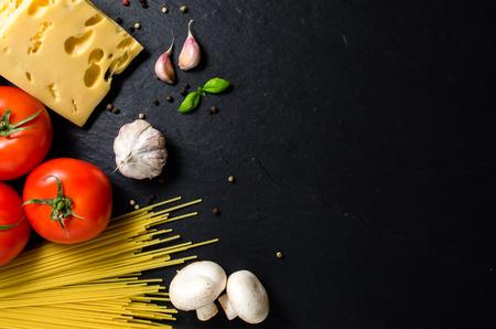 restaurante italiano: Ingredientes del espagueti sobre fondo oscuro Foto de archivo