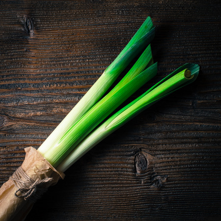 leeks: Fresh leeks on wooden table Stock Photo
