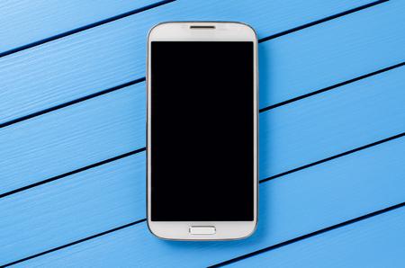 青い木製の背景に黒い画面と白の携帯電話
