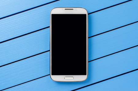 White mobile phone with black screen on blue wooden background