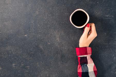 tazas de cafe: Manos femeninas que sostienen la taza de café sobre la mesa oscura