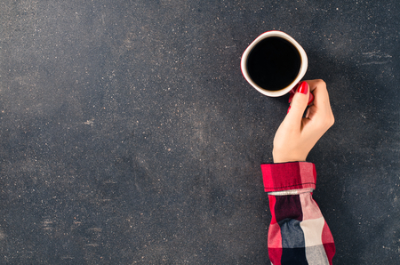Vrouwelijke handen die kop koffie over donkere tafel