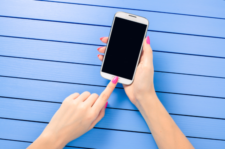 Beautiful female hand using mobile phone over blue wooden table