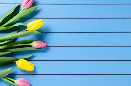 tulipan: Kolorowe tulipany na niebieskim drewnianym stole Zdjęcie Seryjne