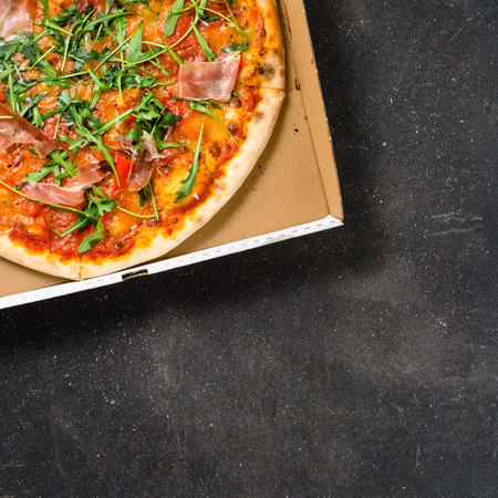 pizza dough: Italian pizza in cardboard box on a dark background