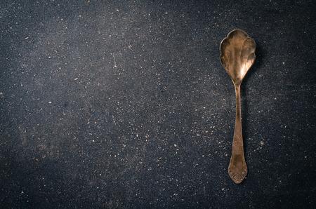 grunge silverware: Old silver spoon on dark background
