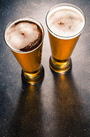 黒いテーブルの上のビールのグラス 写真素材