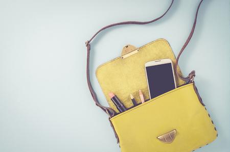 スマート フォンや化粧品の女性のバッグ 写真素材