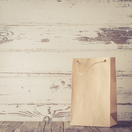 gift bags: Paper gift bag on wooden table