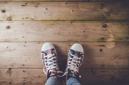 Female sneakers with floral pattern standing on wooden floor
