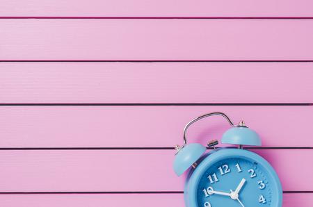 awake: Blue alarm clock on pink wooden background