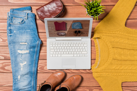 desktop computers: Laptop and autumn clothes on wooden table. Online shopping concept