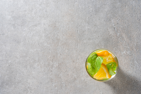alcohol drinks: Refreshing orange drink with mint leaves and ice on gray stone table