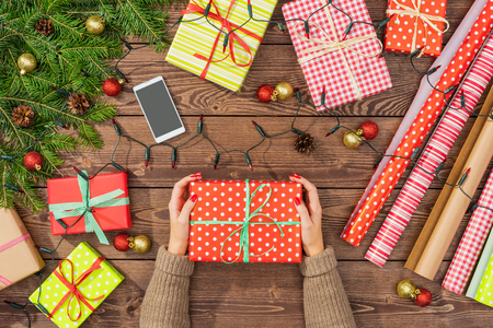 tree decorations: Christmas preparations with gift boxes, wrapping paper and tree on wooden table Stock Photo
