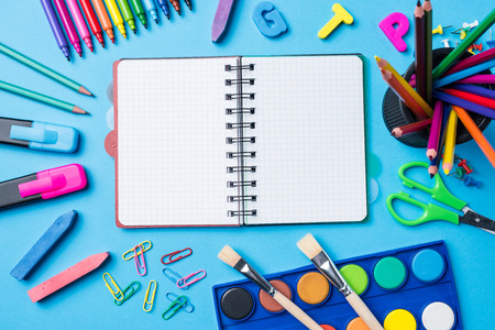Overhead shot of school supplies on blue background Stock Photo