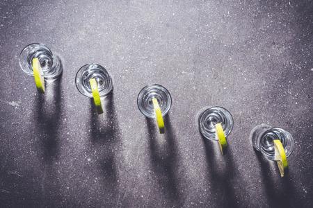 Shot glasses of vodka on dark stone table