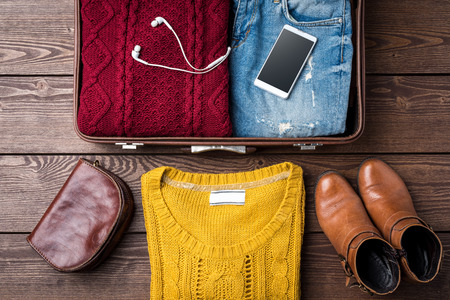 Open suitcase with female casual winter clothes on wooden table. Top view