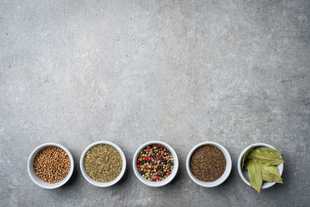 Overhead shot of herbs and spices in white bowls