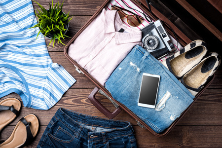 Open suitcase with casual female clothes on wooden table Stockfoto