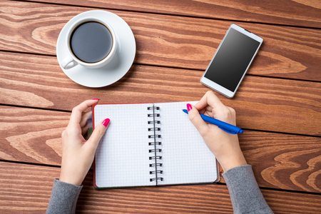 Overhead shot of woman writing in empty notebook Stock Photo