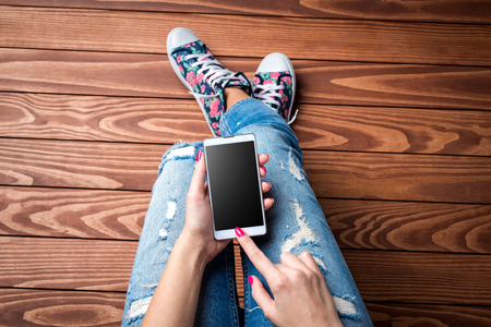 wooden floors: Young woman using smart phone