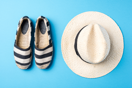 Straw hat and espadrilles on blue background 스톡 콘텐츠