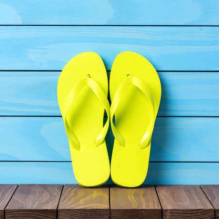 Green flip flops on wooden background. Close up Stock Photo