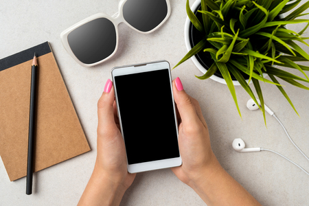 Woman using a smartphone over a gray stone table. Close up Stock Photo