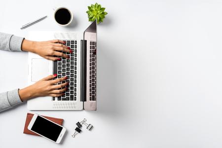 Female hands working on modern laptop. Office desktop on white background
