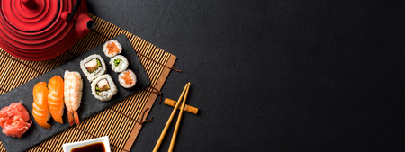 Set of sushi with wasabi, soy sauce and teapot on black stone background Standard-Bild