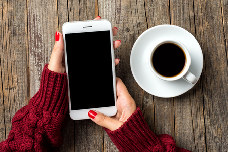 Woman using a smartphone in warm sweater. Close up