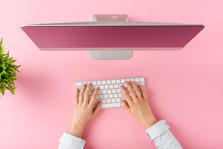 Overhead shot of female hands using computer with accessories on pink background. Office desktop. Flat lay