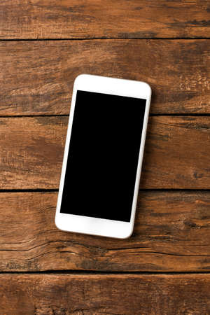 Overhead shot of white smart phone with copyspace on retro wooden background