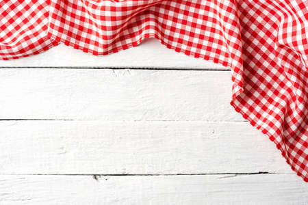 Red checkered tablecloth on white wooden table. Top view Stockfoto